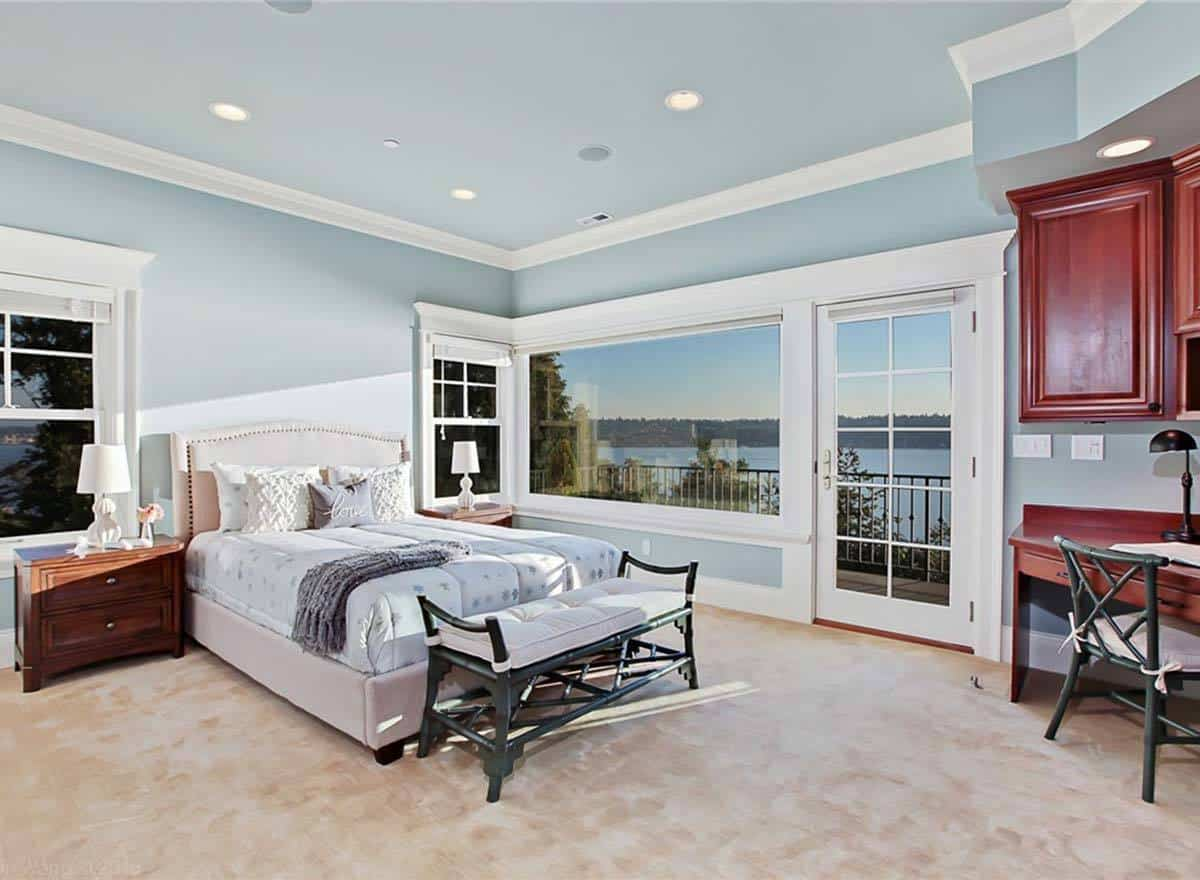 Guest bedroom with beige carpet flooring, sky blue walls, and a glazed door that opens out to the balcony.