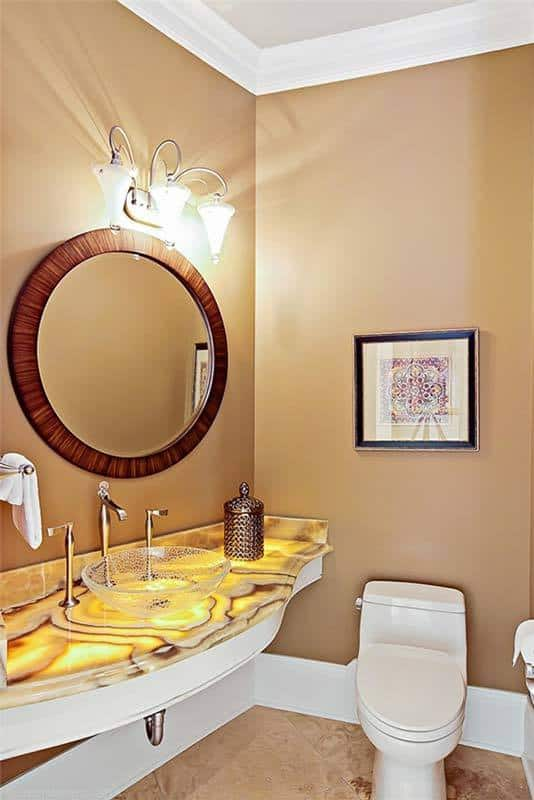 The powder room is equipped with a toilet and a marvelous counter topped with a glass vessel sink.