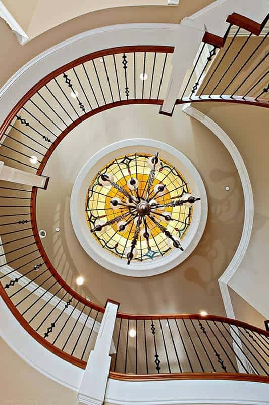 View of the winding staircase from below showing the stunning dome ceiling mounted with a grand chandelier.