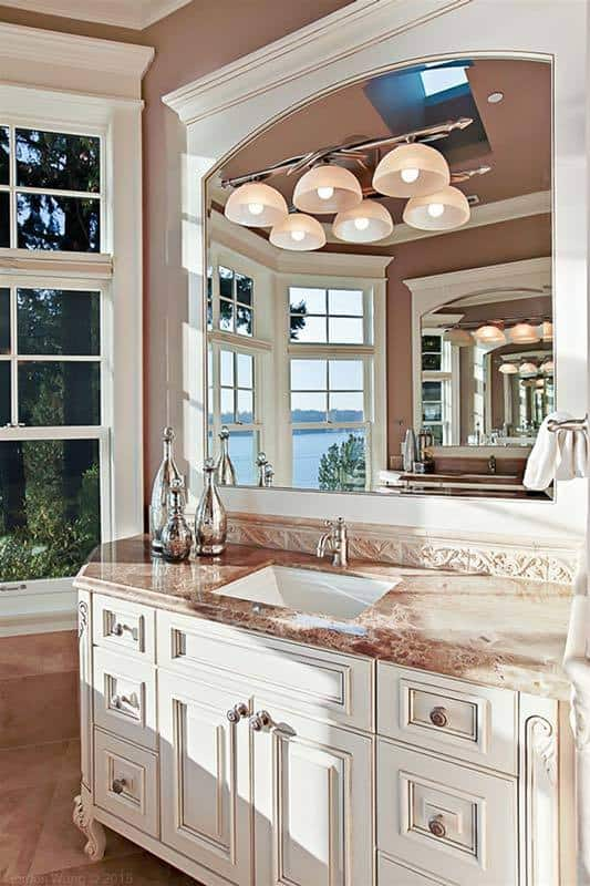 A closer look at the sink vanity shows the elegant countertop and large arched mirror mounted with dome sconces.