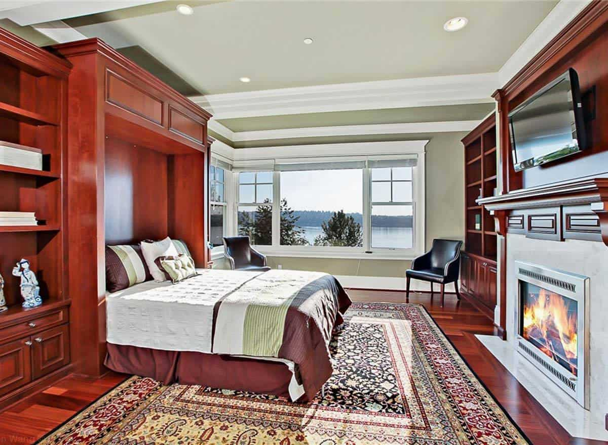 This bedroom has sage green walls, a tray ceiling and rich hardwood flooring matching with the built-ins.