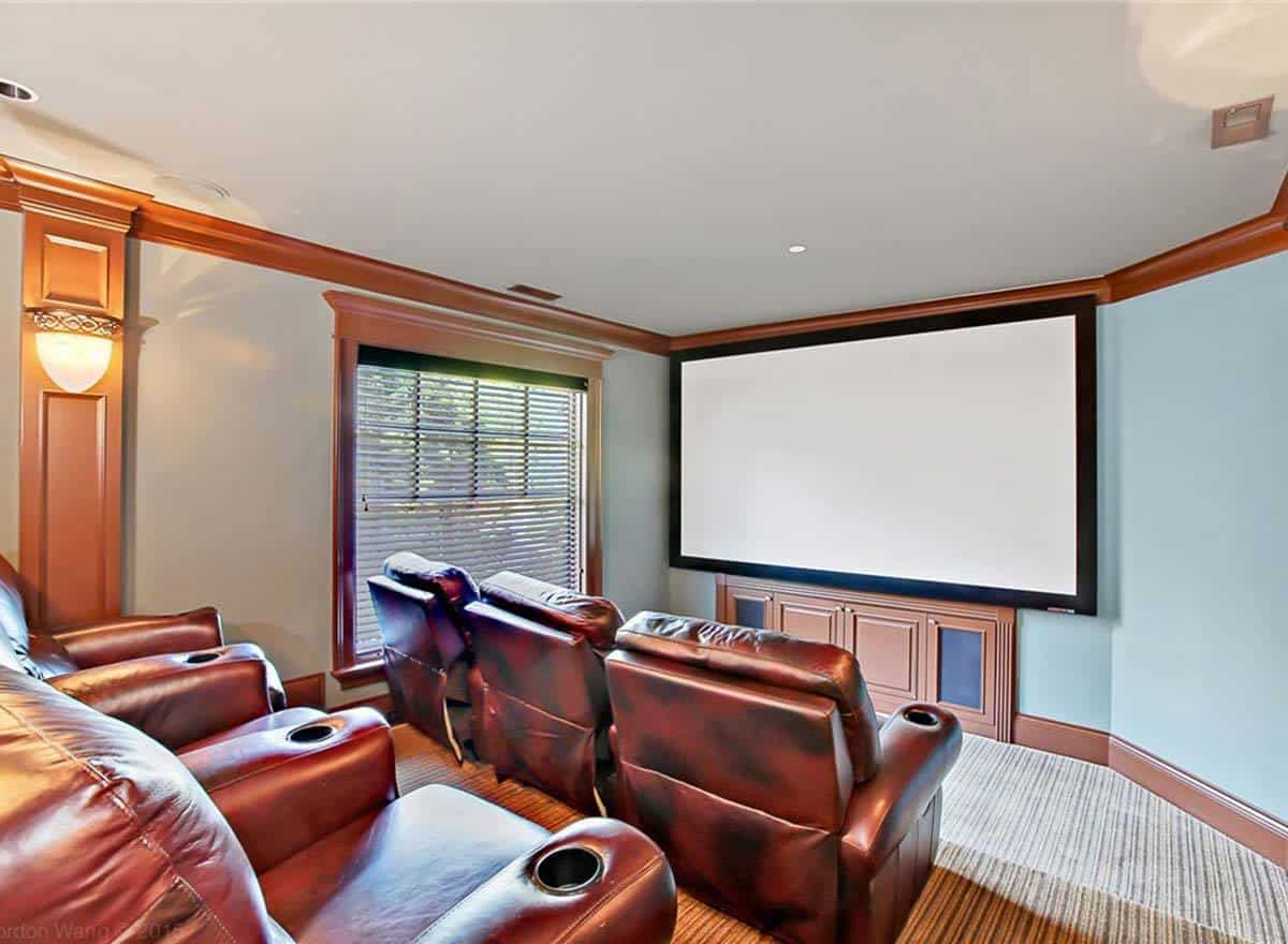 Home theater with brown leather recliners and a large screen fixed against the light blue wall.