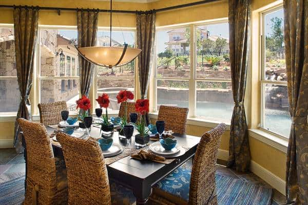 Breakfast nook with wicker dining set and glass-paneled windows overlooking the outdoor pool.