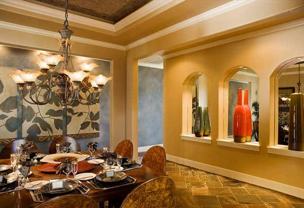 Formal dining room with large vases and a dark wood dining set under the wrought iron chandelier.