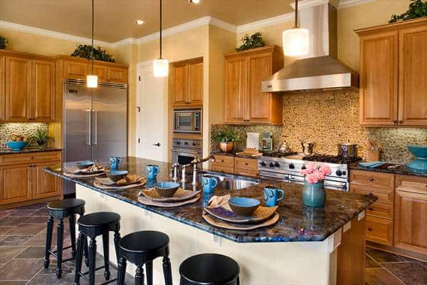 Kitchen with wooden cabinetry and a granite top island complemented with black round barstools.