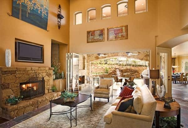 The living room has a warm stone fireplace and folding glass doors that open out to the patio and pool area.