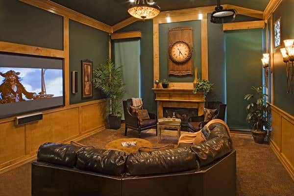 Sunken media room with a curved sofa and a pair of wingback armchairs sitting near the fireplace.