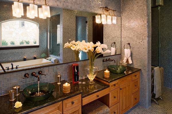 The primary bathroom offers a lengthy vanity topped with dual emerald vessel sinks.