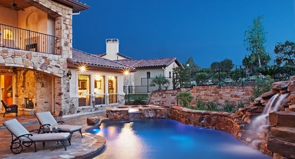 Outdoor space with a covered patio and a stunning swimming pool that's integrated with a hot tub.