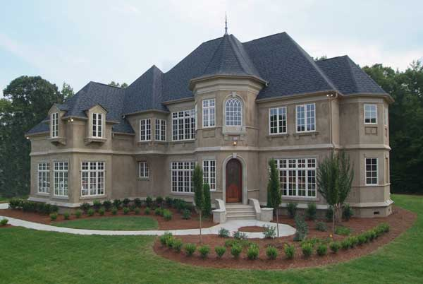 Front exterior view showing the steep roof pitches, arched entry, and a turret housing the foyer.