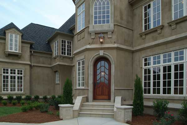 A closer look at the arched entry shows the wooden front door complemented with a tiled staircase.