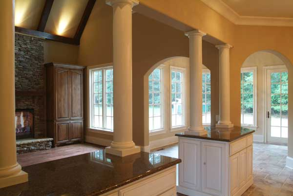 This room has white framed windows, interior arches, and marble columns sitting on the granite top counters.