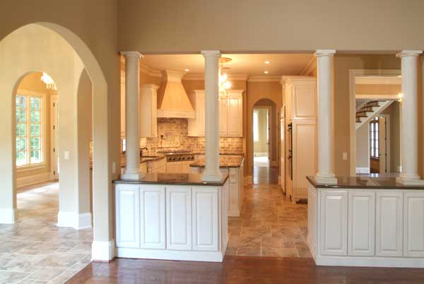 The kitchen is surrounded by open archways and black granite top bars that are lined with white columns.