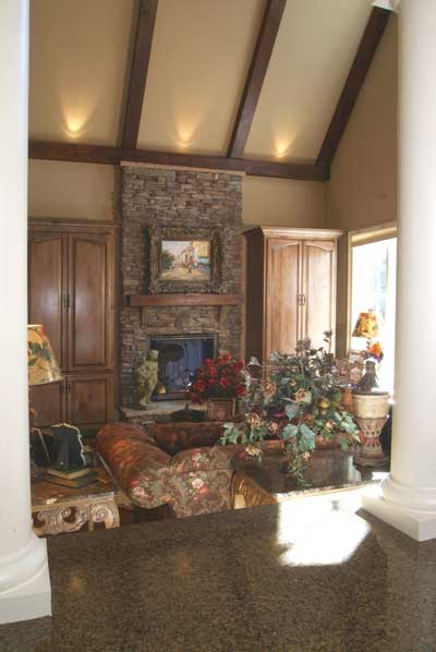 A view of the keeping room from the granite top bar showing the beamed cathedral ceiling and a stone fireplace flanked by wooden cabinets.