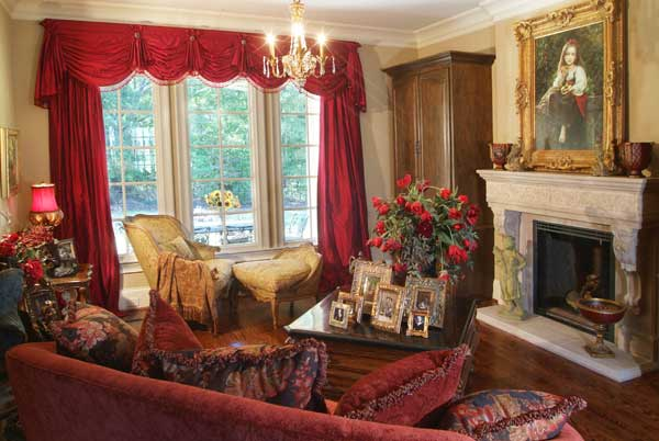 The living room offers a red sofa, a classy lounge chair sitting by the white-framed windows, and another fireplace topped with a lovely gilded portrait.