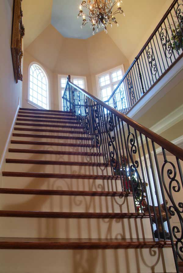 A traditional staircase with intricate railings illuminated by a warm chandelier hanging from the octagonal ceiling.