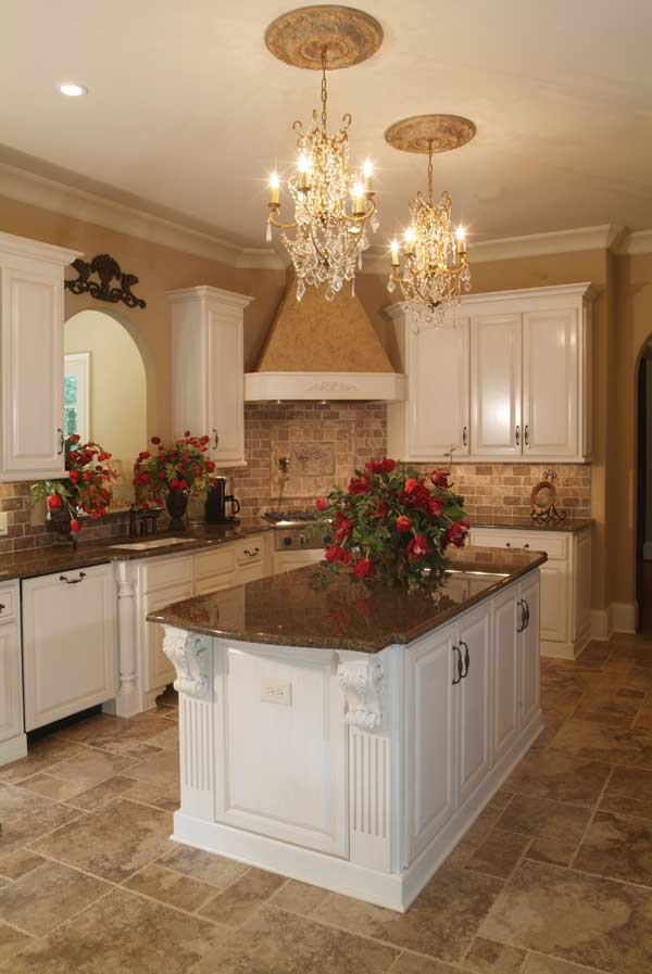 There's also a white center island over limestone flooring lit by a pair of beaded chandeliers.