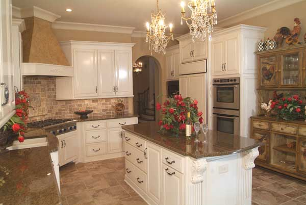 A farther view shows the double wall oven and a rustic display cabinet with decorative sculptures on top.