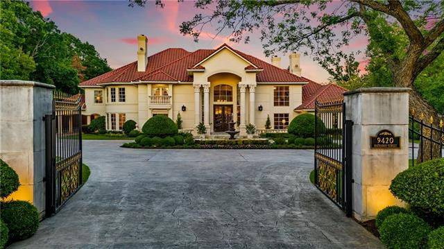 The wrought iron main gate opens to this mansion with clay tile roofing, exterior siding, and greek columns supporting the front porch.