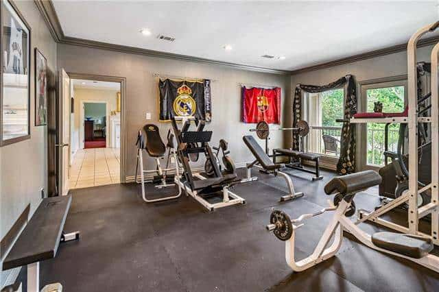 Exercise room with rubber flooring and gray walls adorned by posters and tapestries.