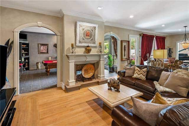 Family room with brown leather sectional and a fireplace nestled in between the archways leading to the game room and patio.