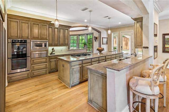 The kitchen offers plenty of counter space and wooden cabinets that blend in with the hardwood flooring.