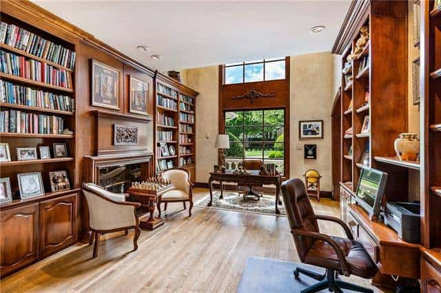 Spacious study with lots of built-ins and desks, and a massive window that invites natural light in.