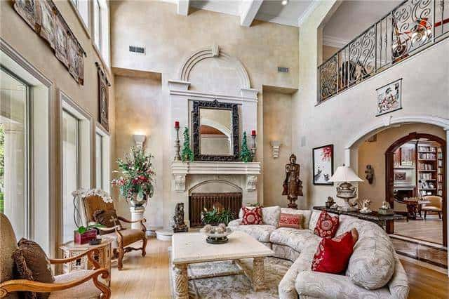 The living room has a soaring beamed ceiling and a fireplace topped with a large ornate mirror.