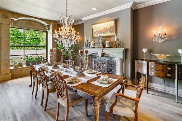 The formal dining room offers a marble fireplace, dark wood buffet and a long dining set illuminated by a warm beaded chandelier.