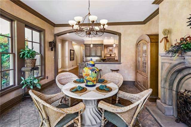 Breakfast nook across the kitchen with tiled flooring and beige walls lined with brown mouldings.
