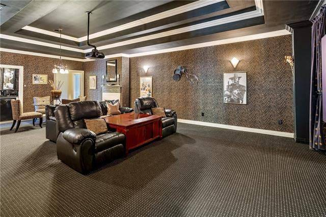 The large media room features a step ceiling and black recliners flanking the polished wooden table.