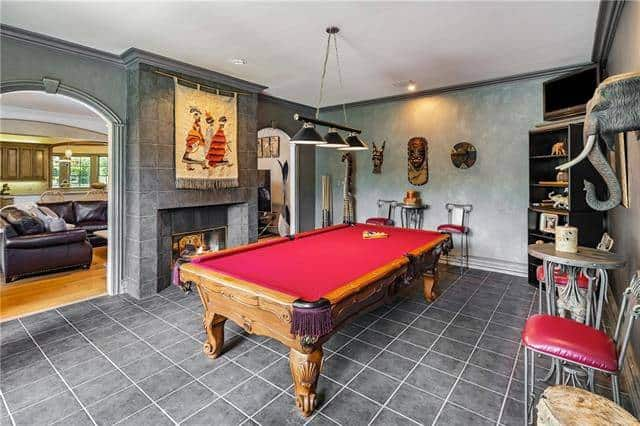 The game room offers multiple seating and a billiard table under the black dome pendants.