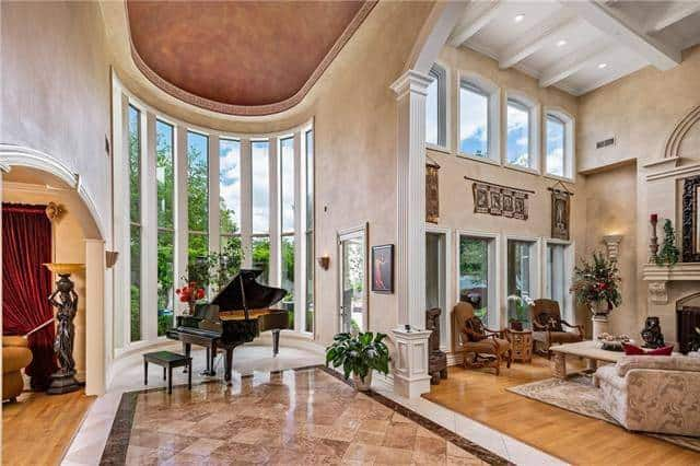 Music room by the curved glass-paneled windows filled with a baby grand piano.