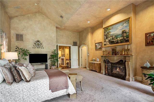 The primary bedroom includes a TV and a romantic fireplace fixed under the beautiful landscape painting.