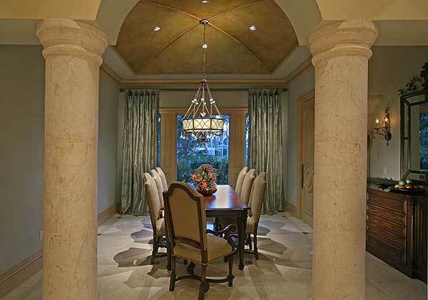 Formal dining room with beige upholstered chairs and a wooden dining table under the drum chandelier.