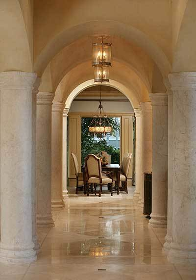A farther view of the dining room shows multiple archways supported by white marble columns.