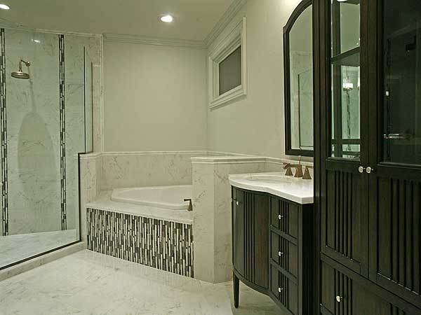 The bathroom offers a walk-in shower, a deep soaking tub and a sink vanity that matches the dark wood cabinet.