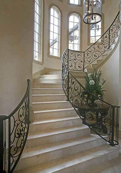 Winding staircase with ornate wrought-iron balustrade and marble steps that blend in with beige walls.