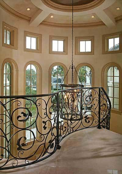 Second-floor loft framed with intricate railings. Ample lighting flows in through the arched windows.