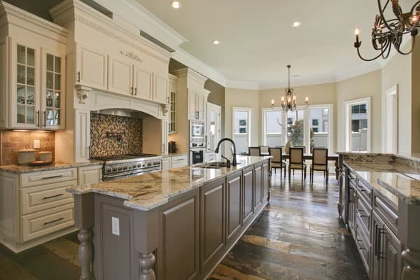 Gourmet kitchen with two granite top islands and a cooking alcove accented with mosaic tile backsplash.