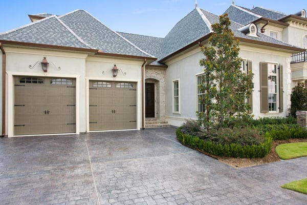 2-car garage with taupe doors and gray walls mounted with lantern sconces.