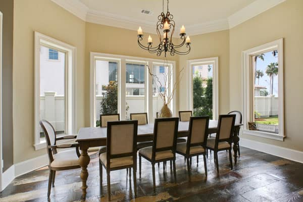 Breakfast nook with a long dining table under the ornate chandelier paired with beige cushioned chairs.