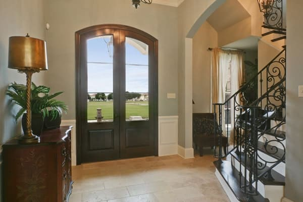 Foyer with dark wood french front door and a carved console table topped by a brass lampshade.