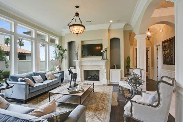 The living room features a romantic fireplace flanked by arch insets that are fitted with cabinets.