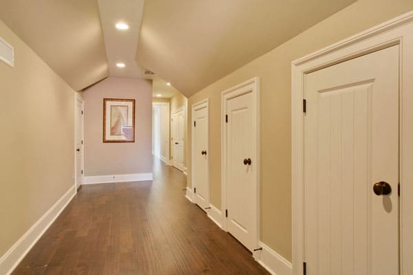 Second-floor corridor with natural hardwood flooring and vaulted ceiling fitted with recessed lights.