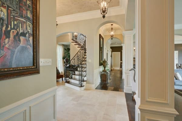 The corridor is illuminated by warm pendants and lined with wainscoted columns and archways.