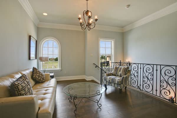 Second-floor loft with cozy seats and a glass top center table matching with the ornate railings and chandelier.