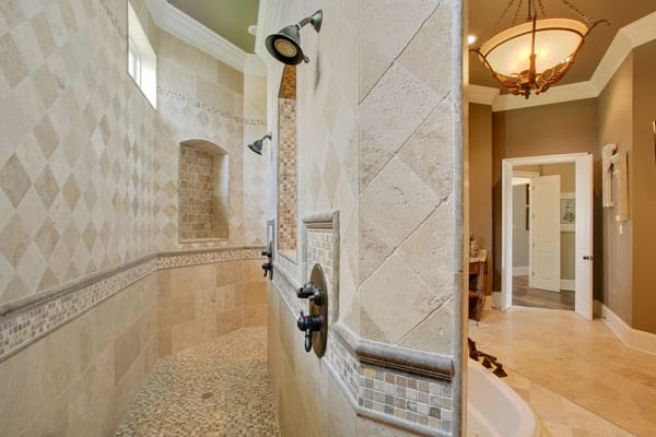 A closer look at the walk-in shower shows the inset shelves and wrought iron fixtures.