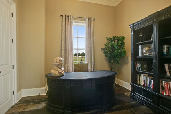 Home office with a dark wood bookcase and a curved desk topped with a bust sculpture.