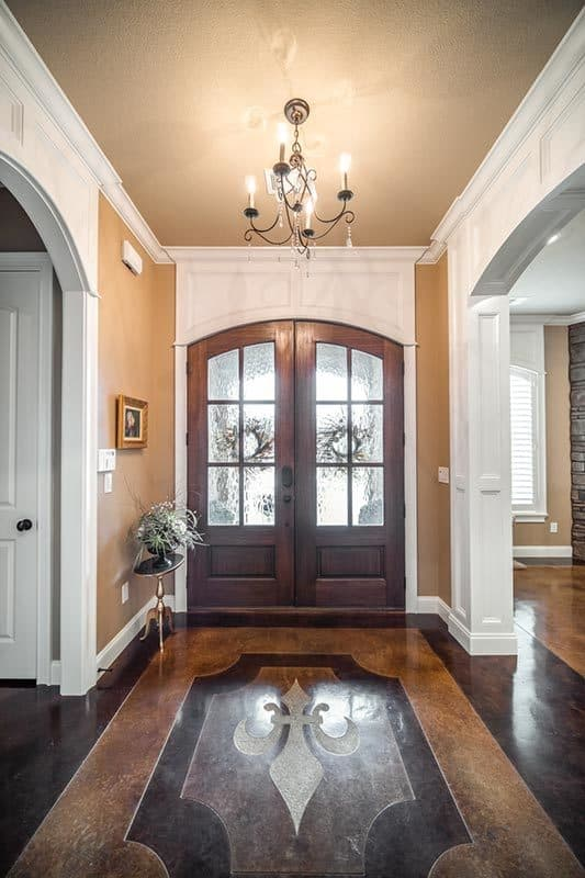 The foyer has a wooden french door and a candle chandelier hanging over the decorative flooring.